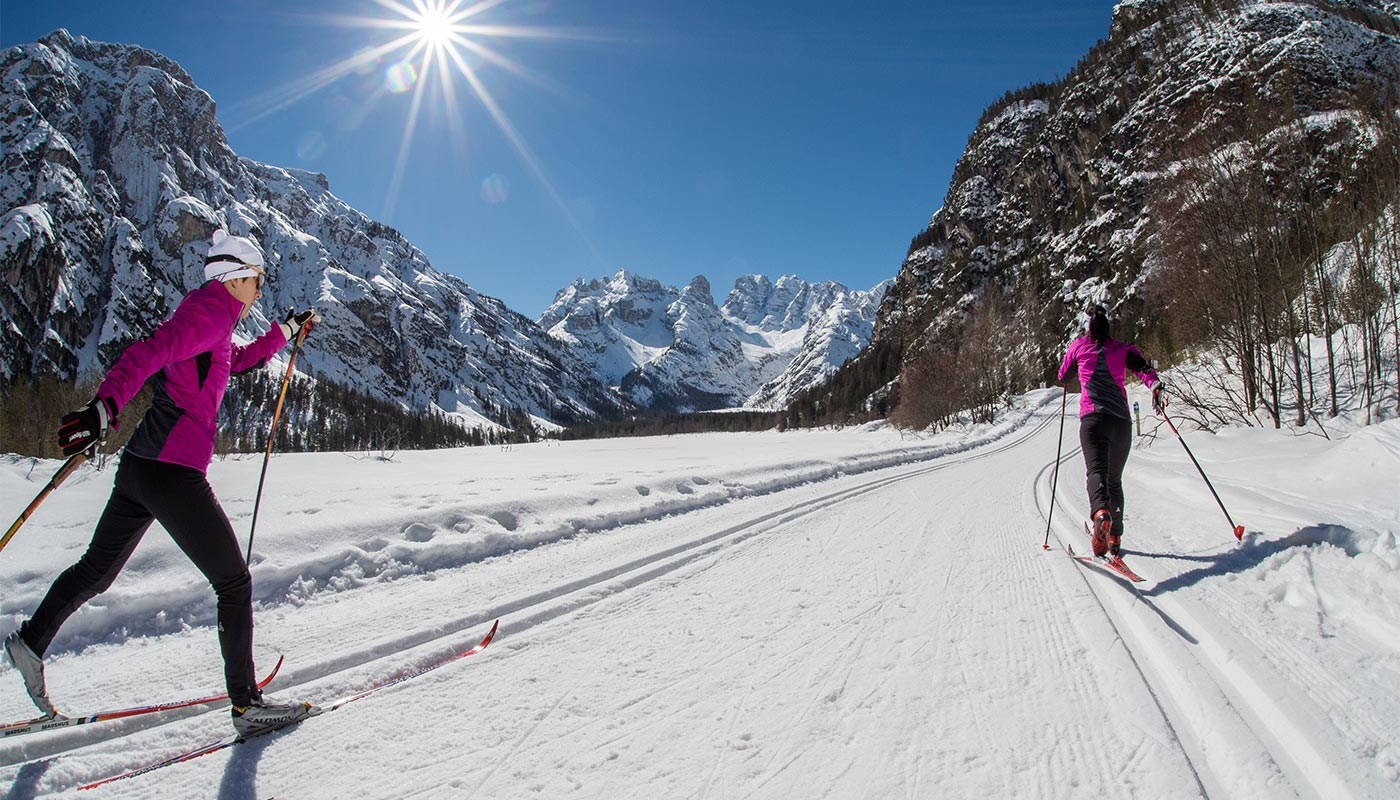 Two girls on a cross-country ski run in Val Pusteria in winter