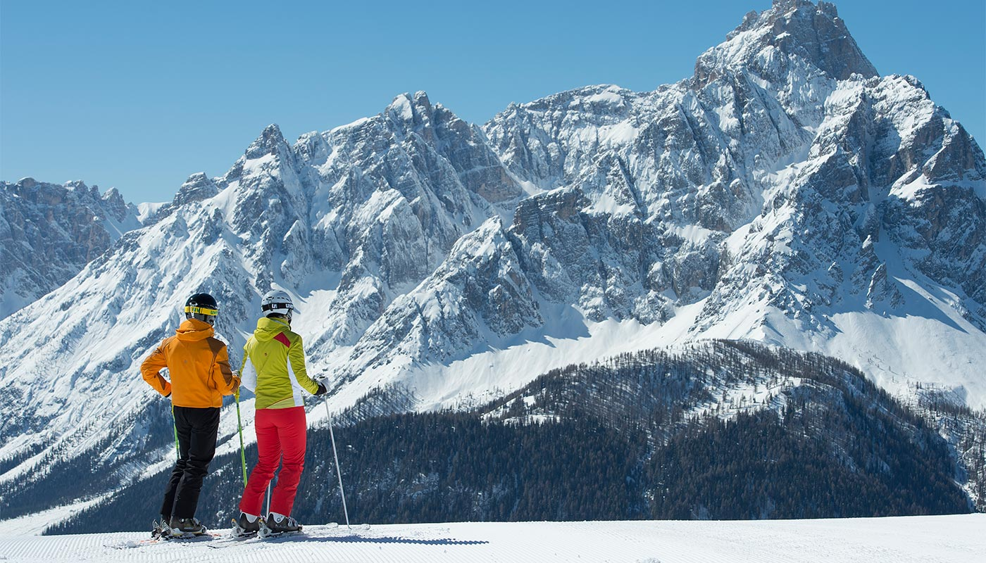 Two boys look at the snowy panorama of the Dolomites